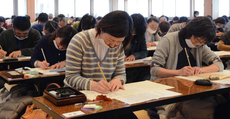 経に息がかからないよう和紙で口を覆い、集中して写経に臨む参加者