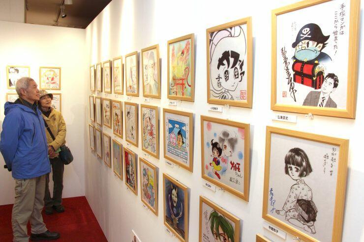 人気漫画家が手塚作品を描いた色紙が並ぶ展示会=13日、新潟市中央区