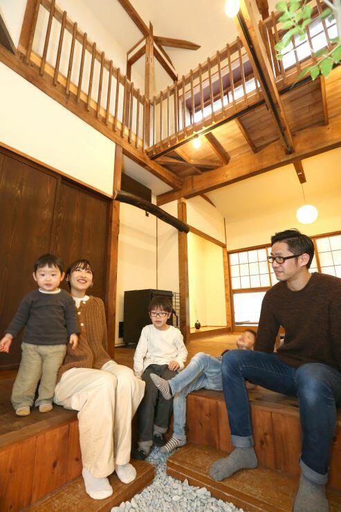 民泊施設「OTONARI」のリビングで家族と座るオーナーの高須雅史さん