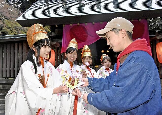 来場者と桜の小枝を交換する19年の福娘=福井県敦賀市の金崎宮