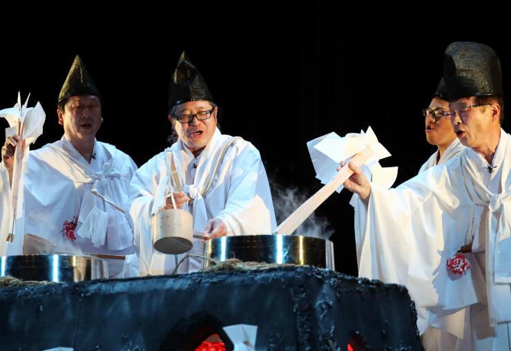 加湿器の蒸気を湯気に見立て、「湯立て神楽」を楽しげに披露する保存会員ら=19日、宮崎市