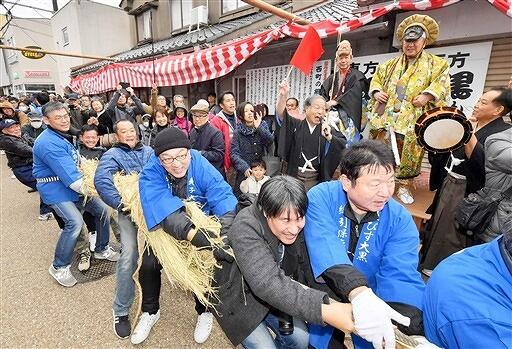 夷子神役、大黒神役の男性2人や大勢の見物客が見守る中、懸命に大綱を引く参加者=1月19日、福井県敦賀市相生町