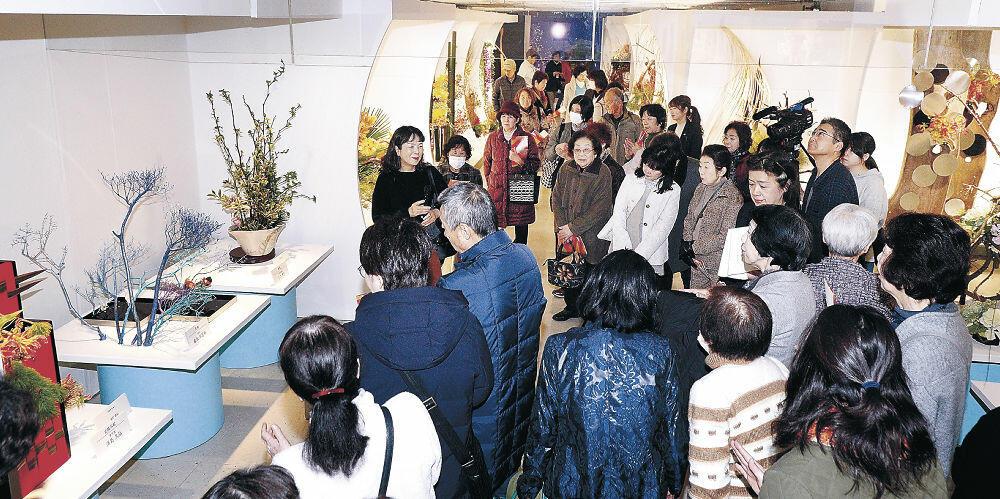 池坊による作品解説で、出品作を鑑賞する来場者=金沢市のめいてつ・エムザ8階催事場
