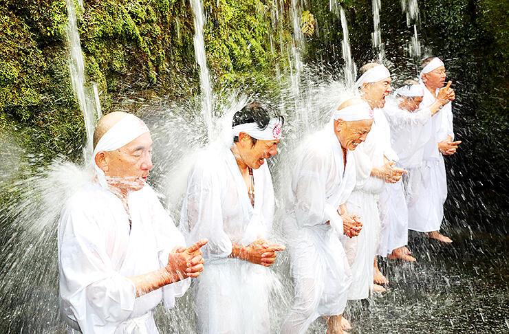 気合を入れ、滝に打たれる人たち=大岩山日石寺
