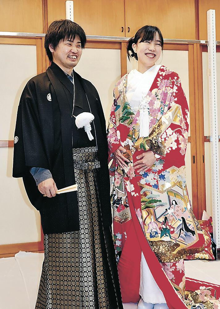 衣装合わせに臨む常橋明浩さんと仁美さん=七尾市内の衣装店