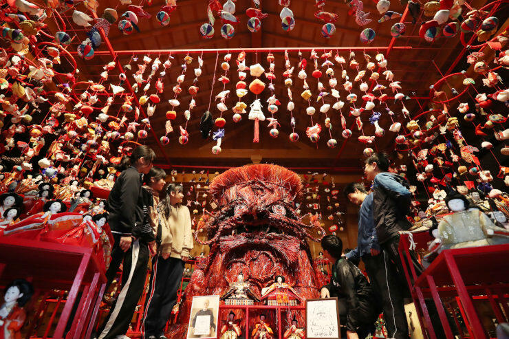 阿智第三小の児童が命名し、ひな人形やつるしびなに囲まれた「ヤークーさま」(中央)=21日、阿智村