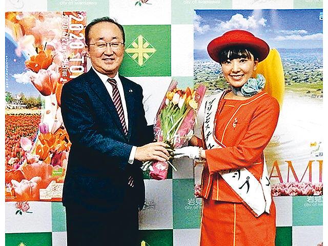 岩見沢市役所で松野市長にチューリップの花束を贈る中島さん(右)