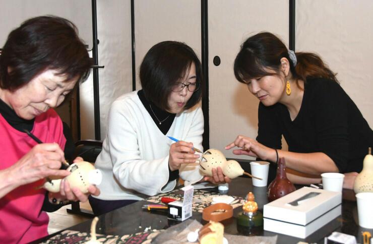 ヒョウタンの切り抜き方を参加者に伝える岩崎さん(右)