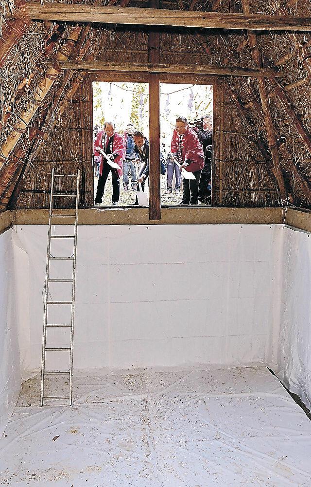 氷室小屋に雪を詰める身ぶりをする関係者=金沢市湯涌町