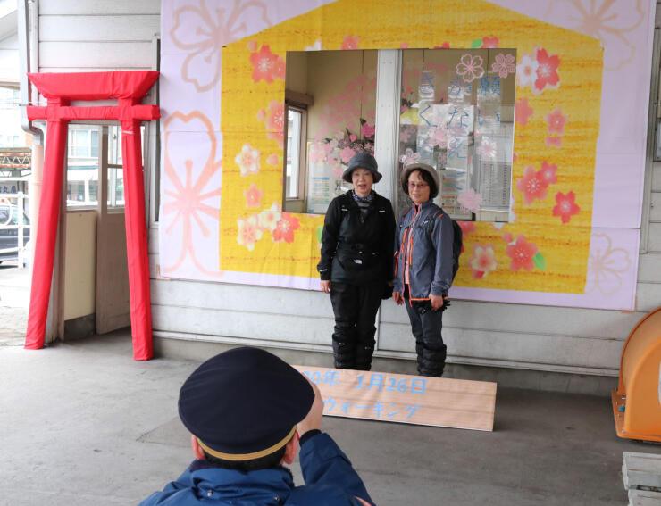 桜町駅で鳥居や絵馬を模した飾りを背景に写真に納まる参加者