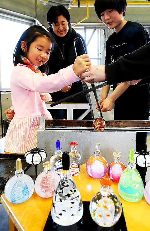 ガラスのひな人形作りを笑顔で体験する子ども=富山ガラス工房