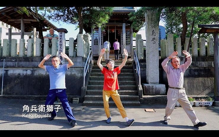 お堂の前で角兵衛獅子のポーズを決める3人。背景にも地元住民が出演している=動画「月潟健康体操」より