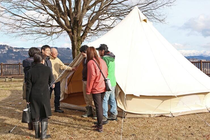 グランピングに用いるテントの様子を確認し、企画について話し合った関係者たち=新潟県小千谷市塩殿