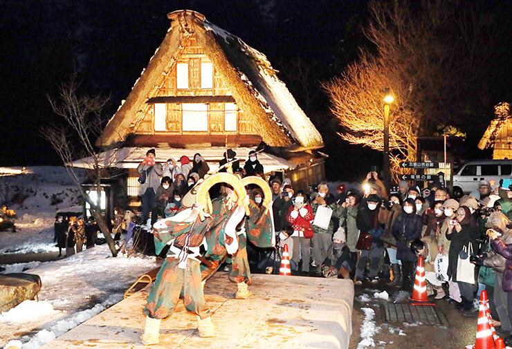 雪化粧しライトアップされた合掌造り集落で披露された「こきりこ」