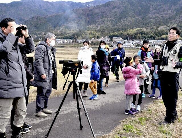 コハクチョウを遠くから観察し生態などについて学ぶ参加者=2月2日、福井県若狭町