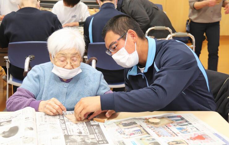 特別養護老人ホームの利用者(左)と木片にやすりをかける高遠高校の生徒=3日、伊那市