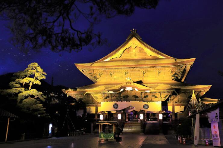 試験点灯で金色に浮かび上がった善光寺本堂=5日午後5時48分、長野市