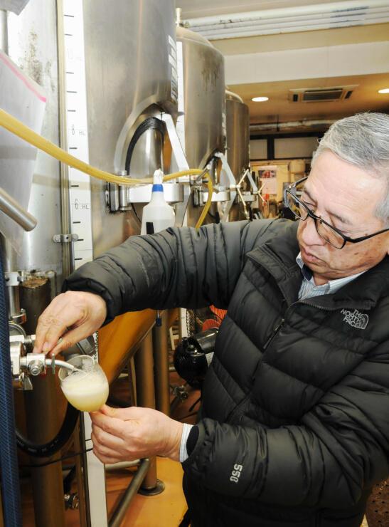 リンゴの果汁を使ったフルーツ発泡酒の出来栄えを確認する小林工場長