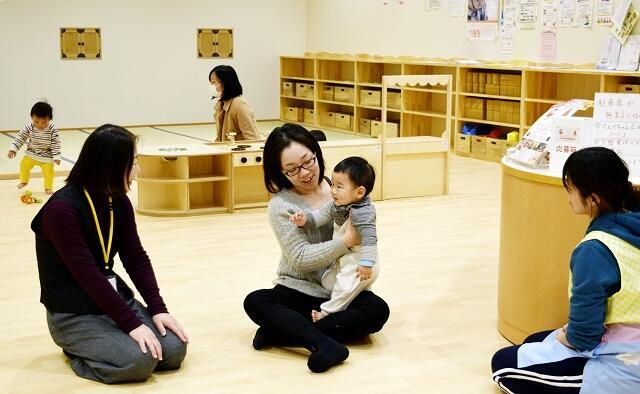 てんぐちゃん広場を利用する親子連れと子育て支援センターのスタッフ=昨年12月、福井県越前市のアルプラザ・武生3階