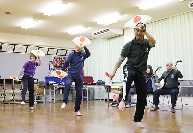 扇子を手に初稽古する宮坂会長(左から2人目)ら
