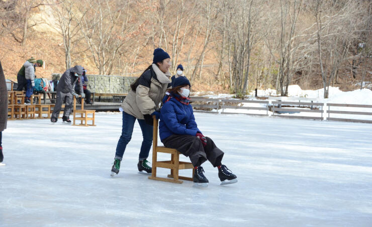 山あいにあるケラ池でスケートを楽しむ観光客