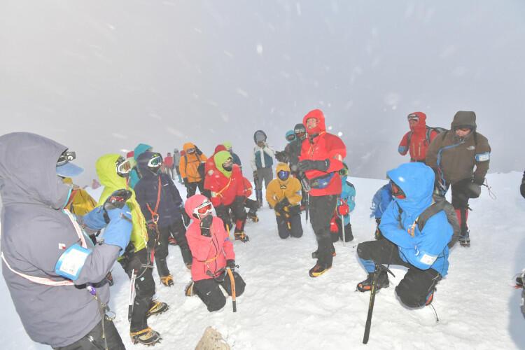 丸山近くの稜線で、強風に飛ばされない姿勢などを学ぶ参加者たち=8日午後5時15分
