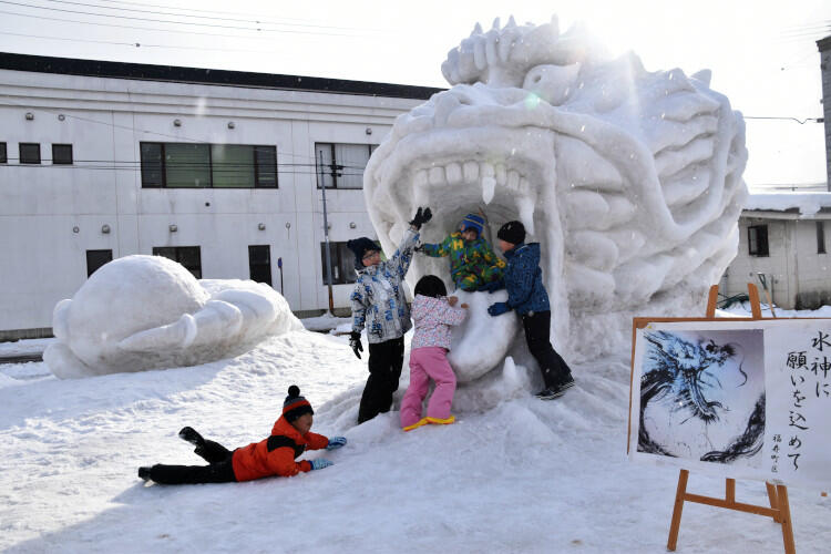福寿町区の住民が作った「龍」の雪像。龍の右手(左奥)は雪玉を握っている=8日午後3時4分、飯山市