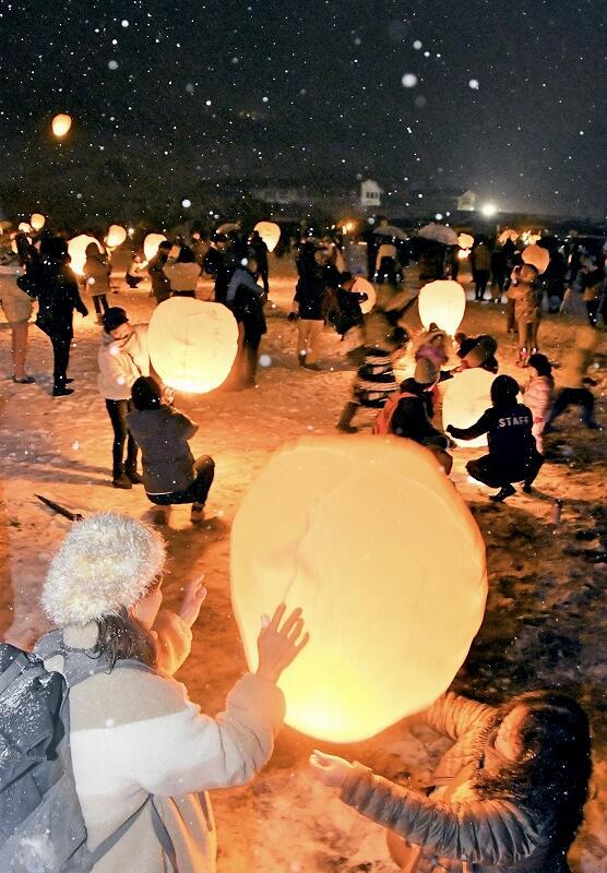 スカイランタンを夜空に放つ参加者たち=2月8日夜、福井県大野市南六呂師