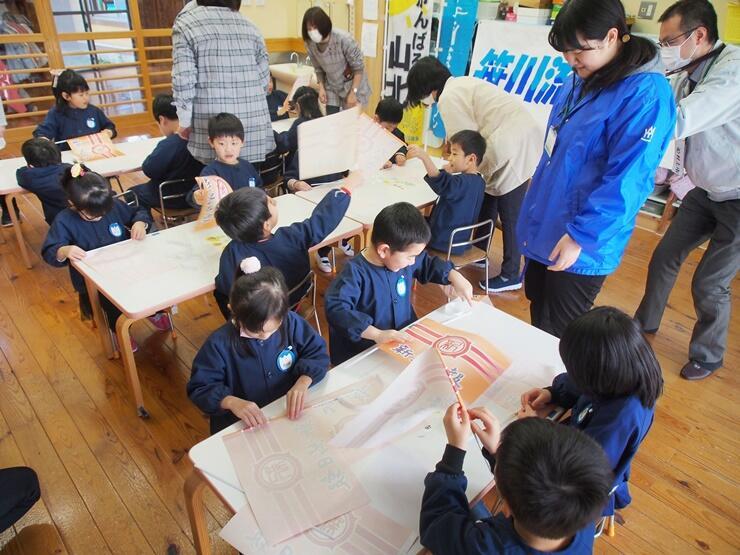 笹川流れマラソンの応援手旗を作る園児たち=村上市