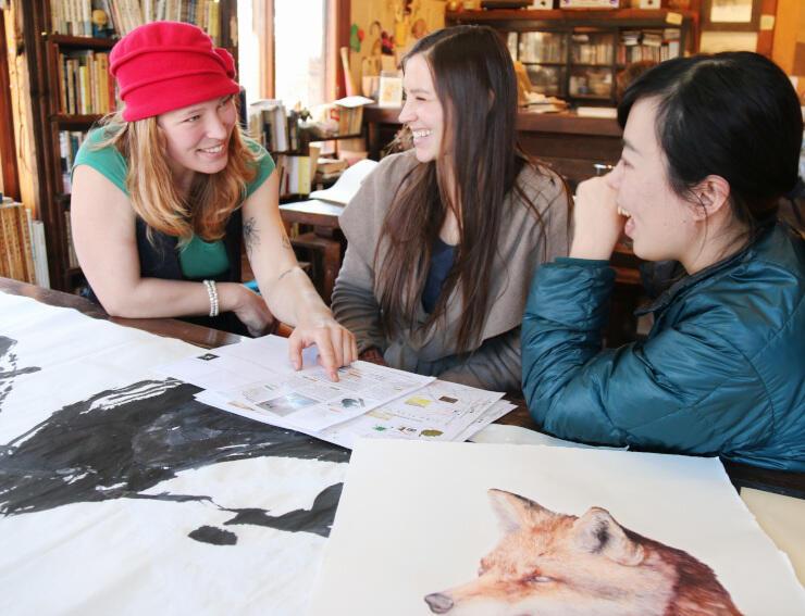 地図の英文表記を確認する(左から)ブリルビカスさん、カントーラさんら。手前の絵画は2人の作品