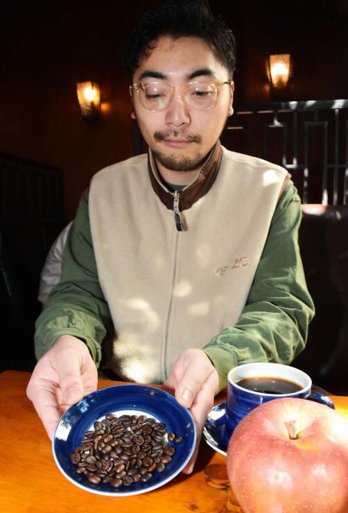 リンゴの果肉と一緒に発酵させた「信州林檎コーヒー」を紹介する斉藤さん