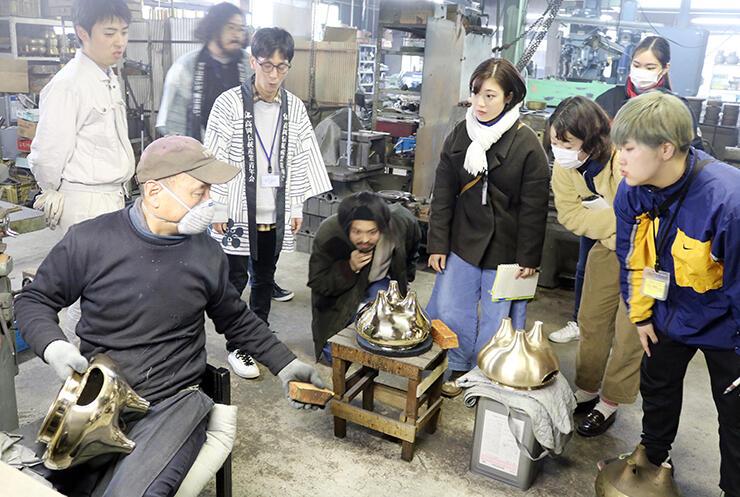 般若鋳造所で職人から金属の研磨作業について説明を受ける学生ら