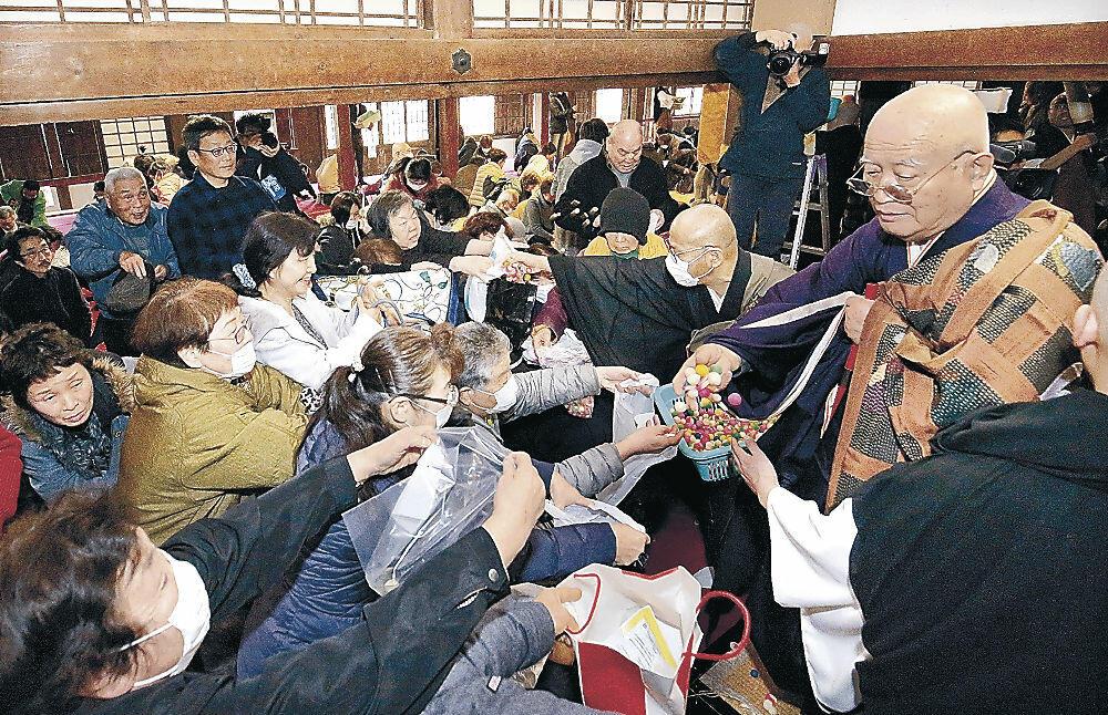 涅槃団子に手を伸ばす参列者=長坂町の大乘寺