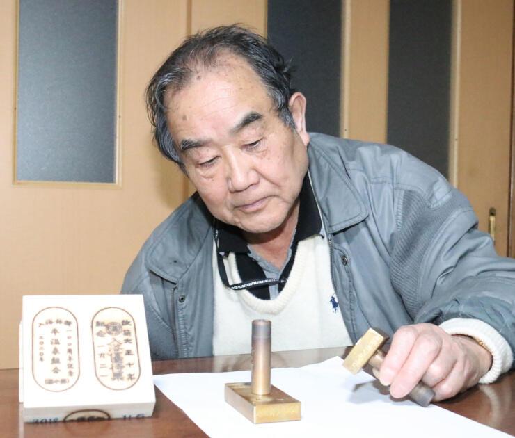平湯の100周年を記念して作った金属製のはんこを手にする鉄羅さん