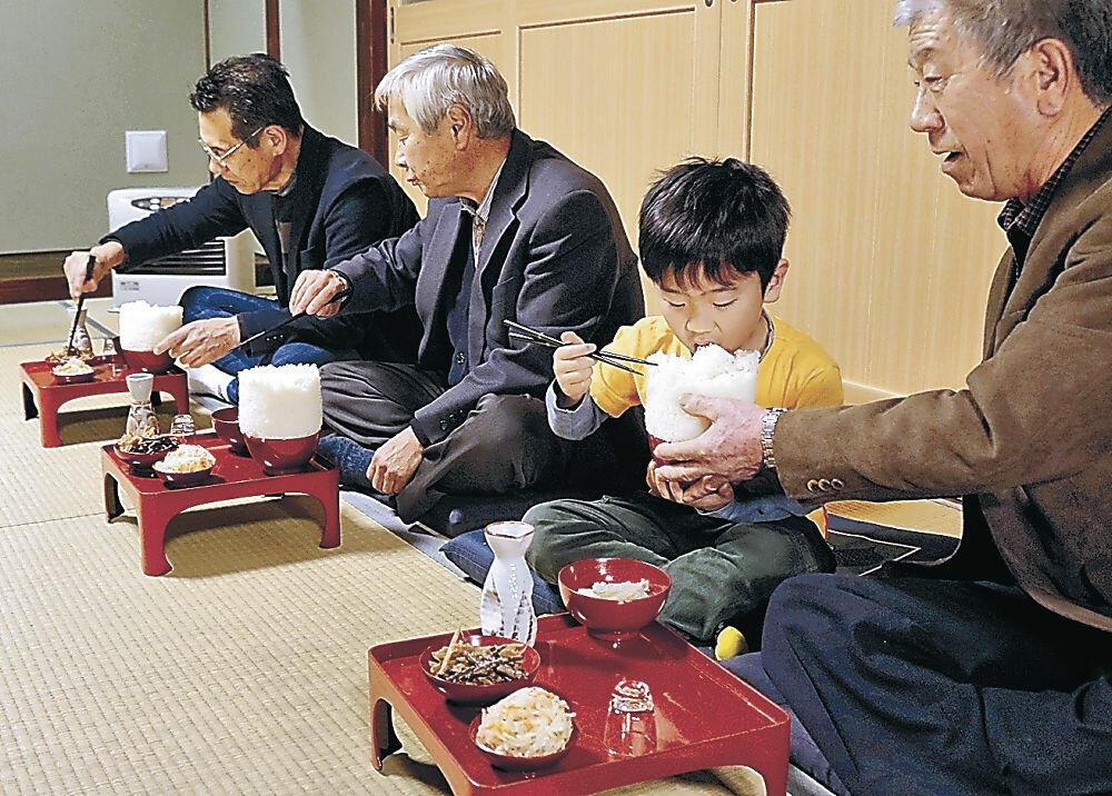 円柱状に盛られた「もっそう飯」を食べる参加者=輪島市久手川町