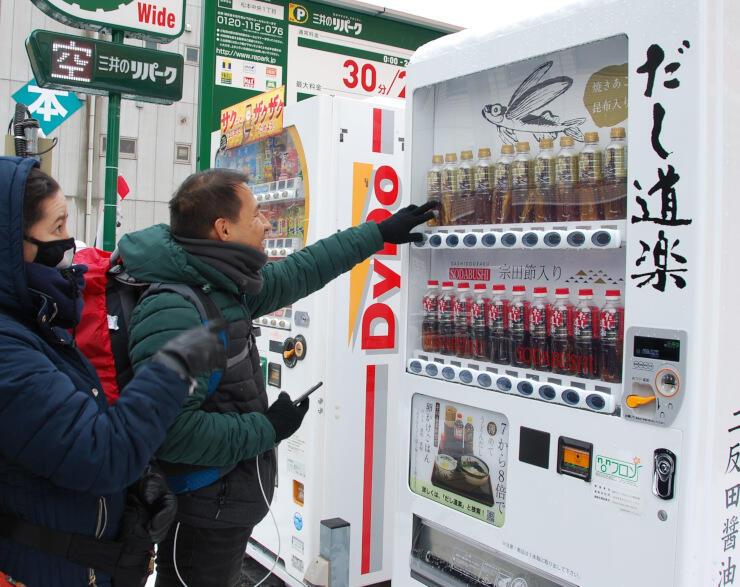 ペットボトル入りの「だし」が並ぶ自動販売機。通り掛かった人たちも興味深そう=松本市