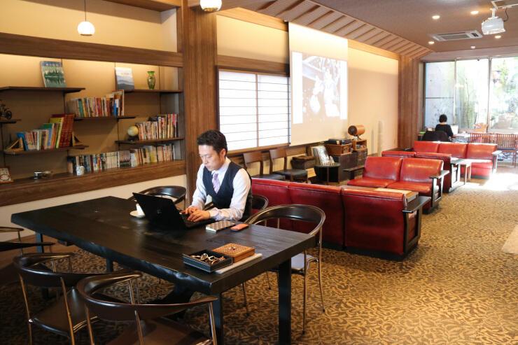 南條旅館のロビーで作業をする鈴木さん