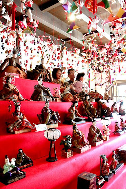 ひな人形と記念写真に納まる家族連れ(奥)=22日、小諸市のほんまち町屋館