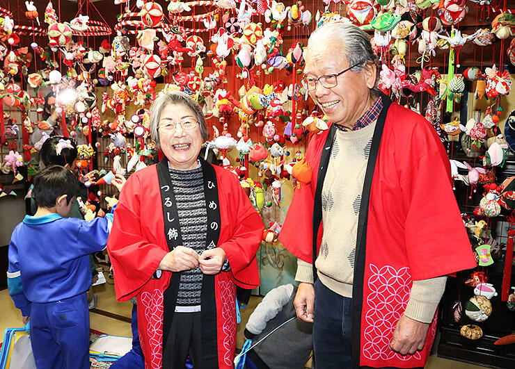 心を込めて作ったつるし飾りに囲まれ、笑顔で過去10回の展示を振り返る三品さん夫妻