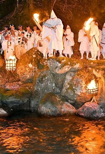 かがり火で照らされた遠敷川に御香水を注いだ「お水送り」=3月2日午後9時ごろ、福井県小浜市下根来の鵜の瀬