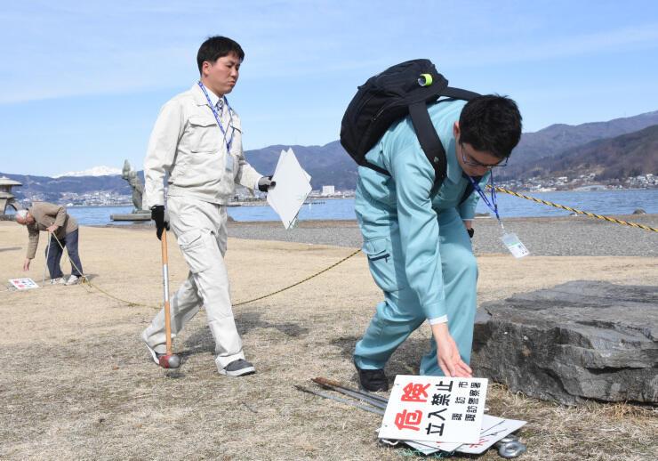 諏訪湖の結氷に備えて設置した看板とロープの撤去作業=3日午前9時半すぎ、諏訪市湖岸通り