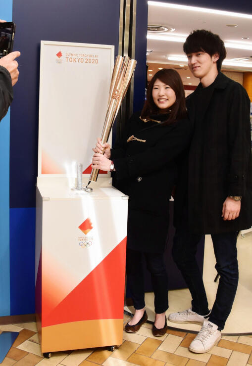 東京五輪の聖火リレートーチを手に記念撮影をする来店客=5日、松本市