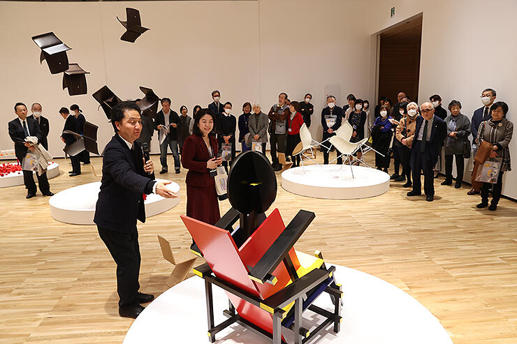 椅子をインスタレーションのように飾った会場で、展示の狙いを説明する森村さん(手前左)=県美術館