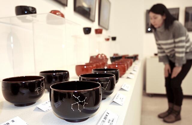 星をテーマにした漆器や写真が並ぶ展示会=3月6日、福井県福井市中央1丁目のふくい工芸舎
