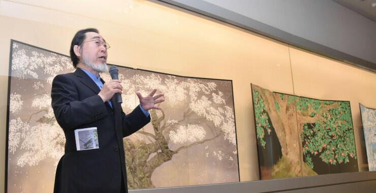 桜やツバキを描いたびょうぶ絵の前で解説する中島さん