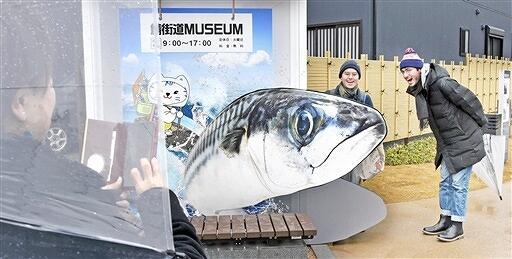 小浜市鯖街道ミュージアムのトリックアートの前で撮影するグループ=3月8日、福井県小浜市広峰