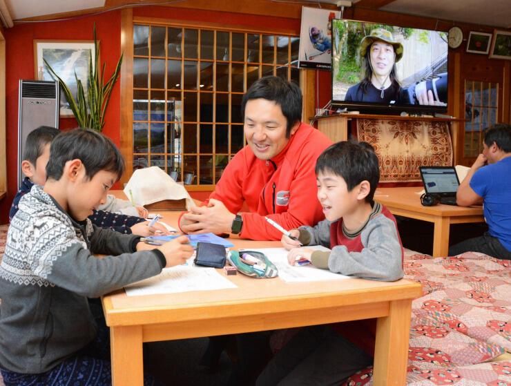 滞在中の小学生の面倒を見る「幸の湯」の社員(中央)=山ノ内町