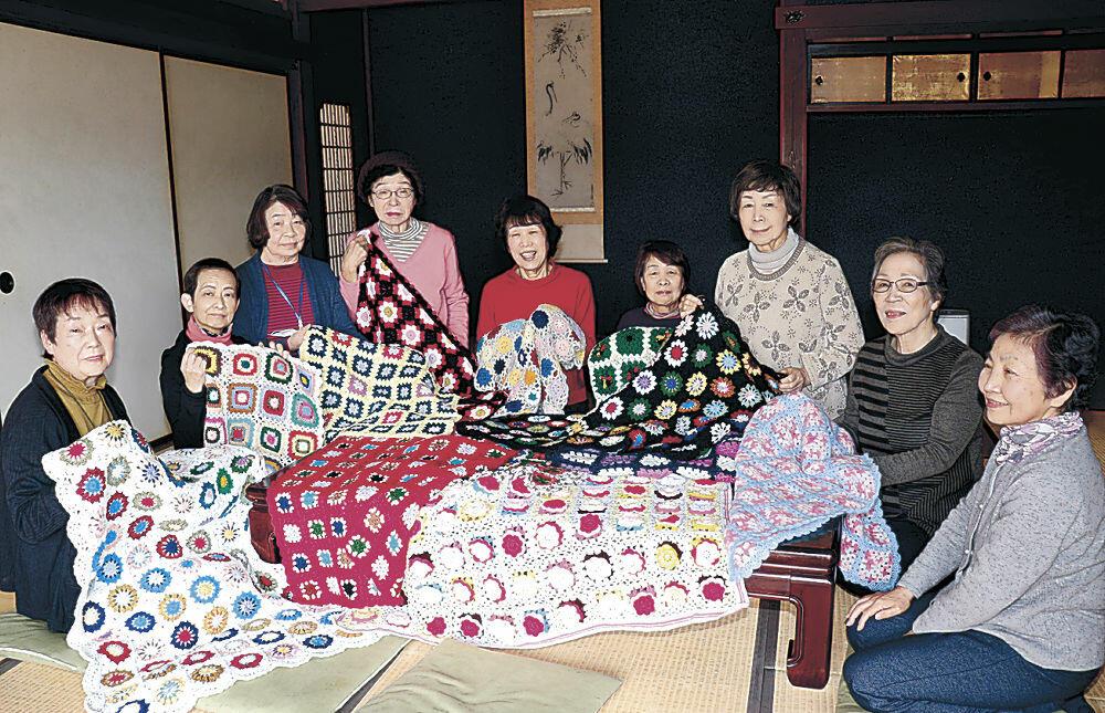 手作りの膝掛けを広げるメンバー=加賀市熊坂町の蘇梁館