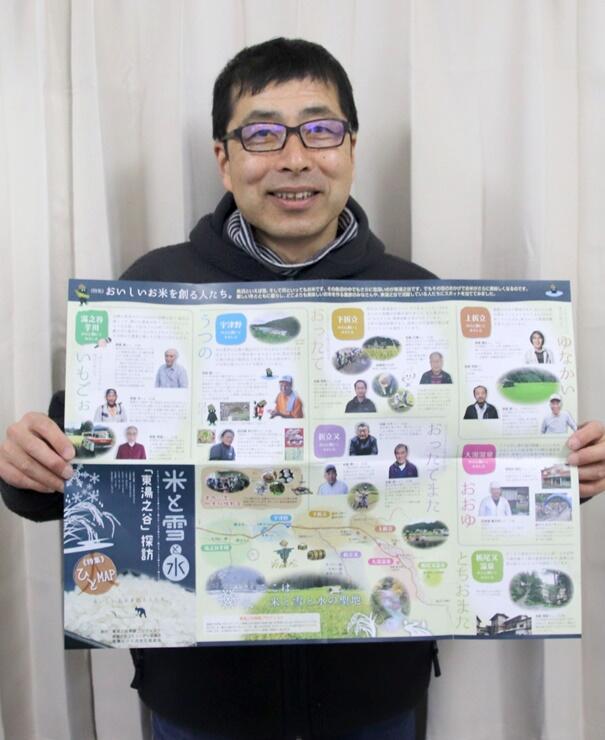 制作を担当し、完成したマップを持つ地域おこし協力隊員の佐藤守一さん=魚沼市の湯之谷公民館