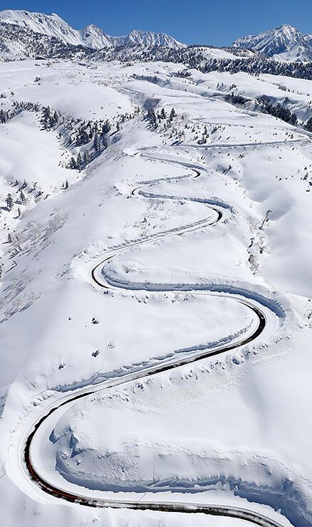 除雪され雪原に曲線を描く七曲付近の高原バス道路=12日午前10時35分ごろ、本社チャーターヘリから